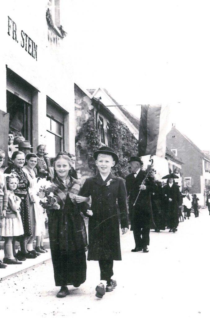 Beim Umzug am Heimattag im Juli 1956 in der Oberen Gasse vor dem Gemischtwarenladen Stein.