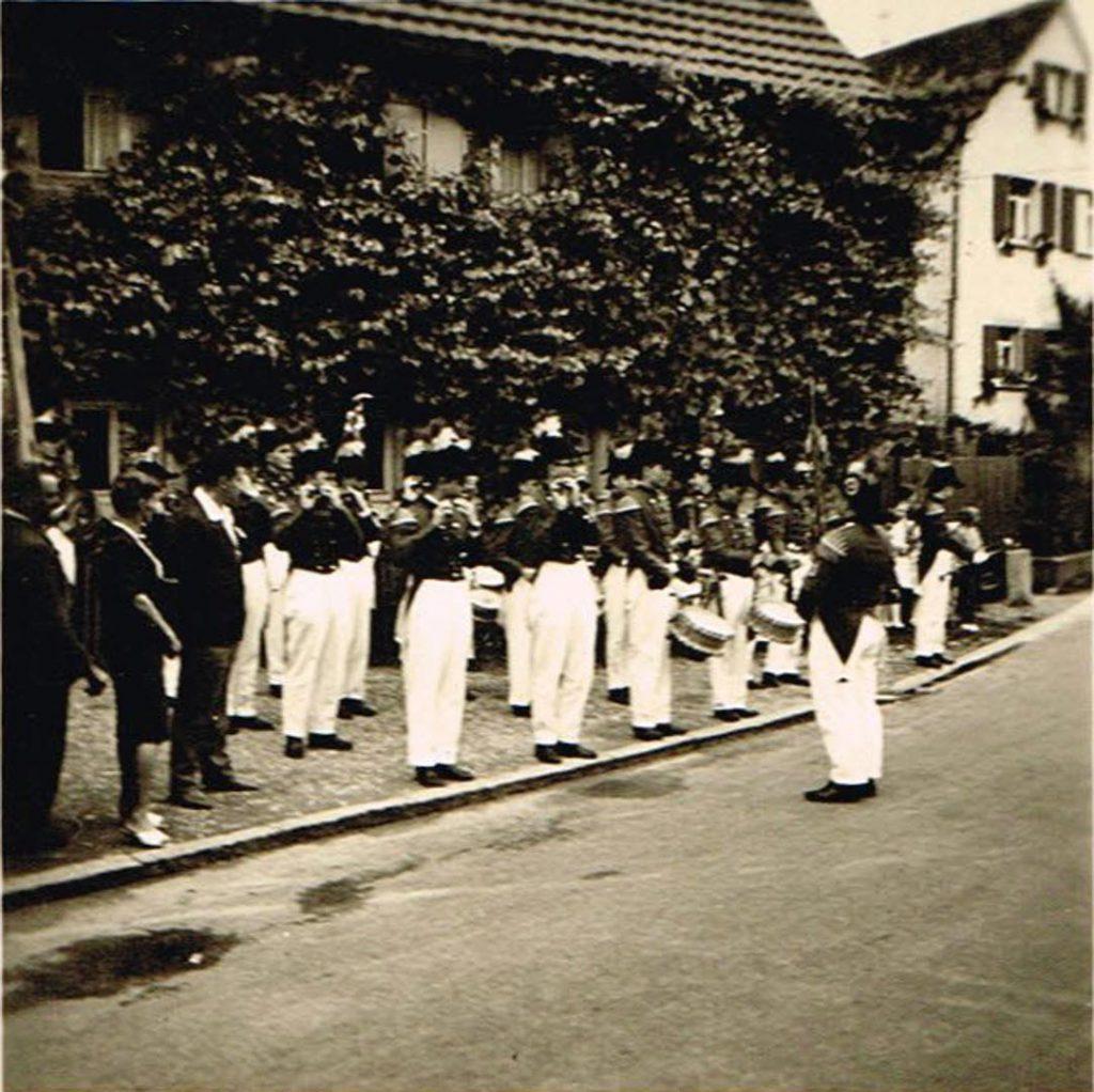 Der am 06. Juni 1952 gegründete langenburger Spielmanns- und Fanfarenzug beim Heimattag 1957. Gut zu erkennen an den schwarzen Zweispitz- Hüten mit den rot-weißen Federbüschen, roten Jacken und die weißen Hosen mit schwarz-goldenen Tressen. Rot-Weiß stand für das Haus Hohenlohe, Schwarz-Gold für die Stadt Langenburg.
