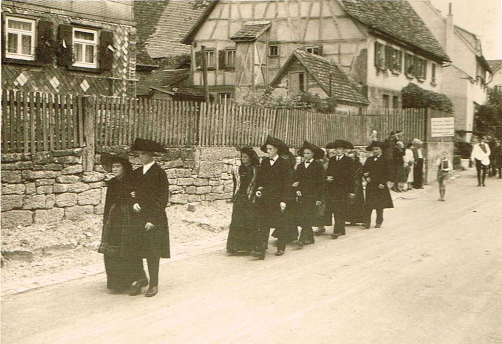 Trachtengruppe auf der Dorfstraße beim Umzug am Heimattag 1957.