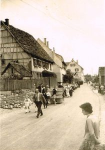 Vorne in der Mitte: Jakob Kist auf der Dorfstraße beim Heimattag 1957. Die Frau vorne rechts ist nicht bekannt. Im Hintergrund von links die Häuser: Bickelmann, ehemals Burkhard, Mahr & Christ, danach das abgerissene Haus Bolz / Ziegler / Horlacher, dann das alte Rathaus  / Schulhaus.