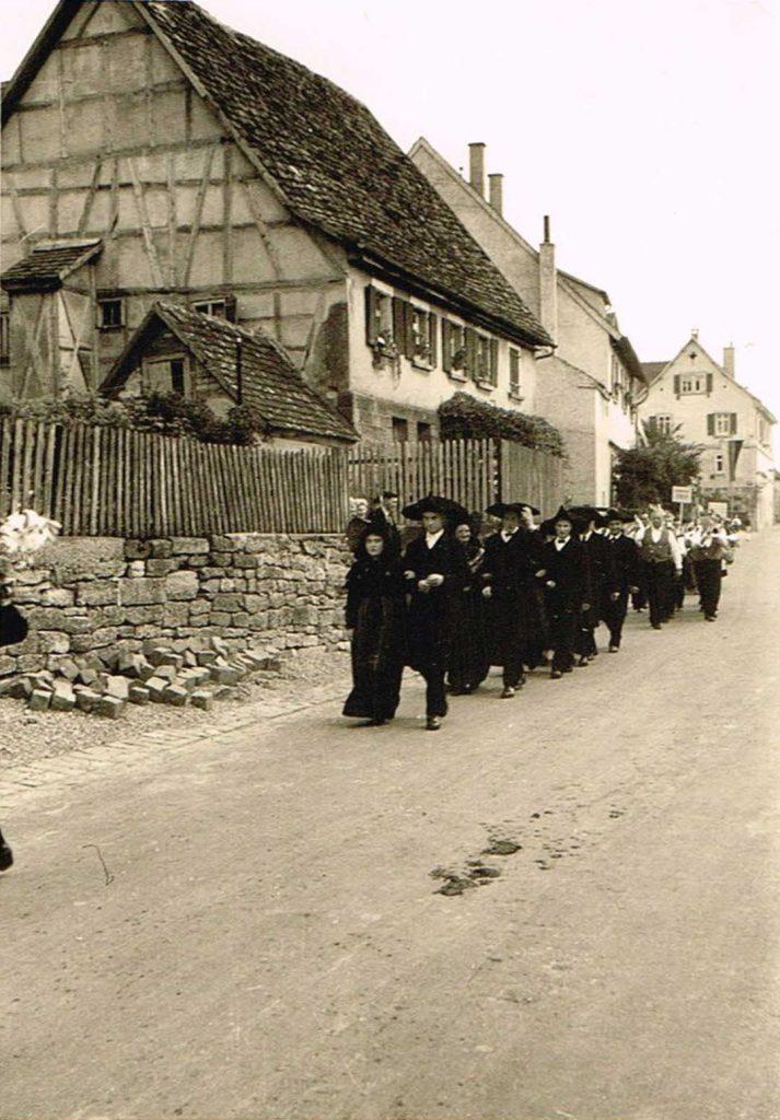 Vorne Trachtengruppe, dahinter eine unbekannte Musikkapelle auf der Dorfstrasse beim Heimattag 1957. Im Hintergrund von links die Häuser: Bickelmann, ehemals Burkhard, Mahr & Christ, danach das abgerissene Haus Bolz / Ziegler / Horlacher, dann das alte Rathaus / Schulhaus.