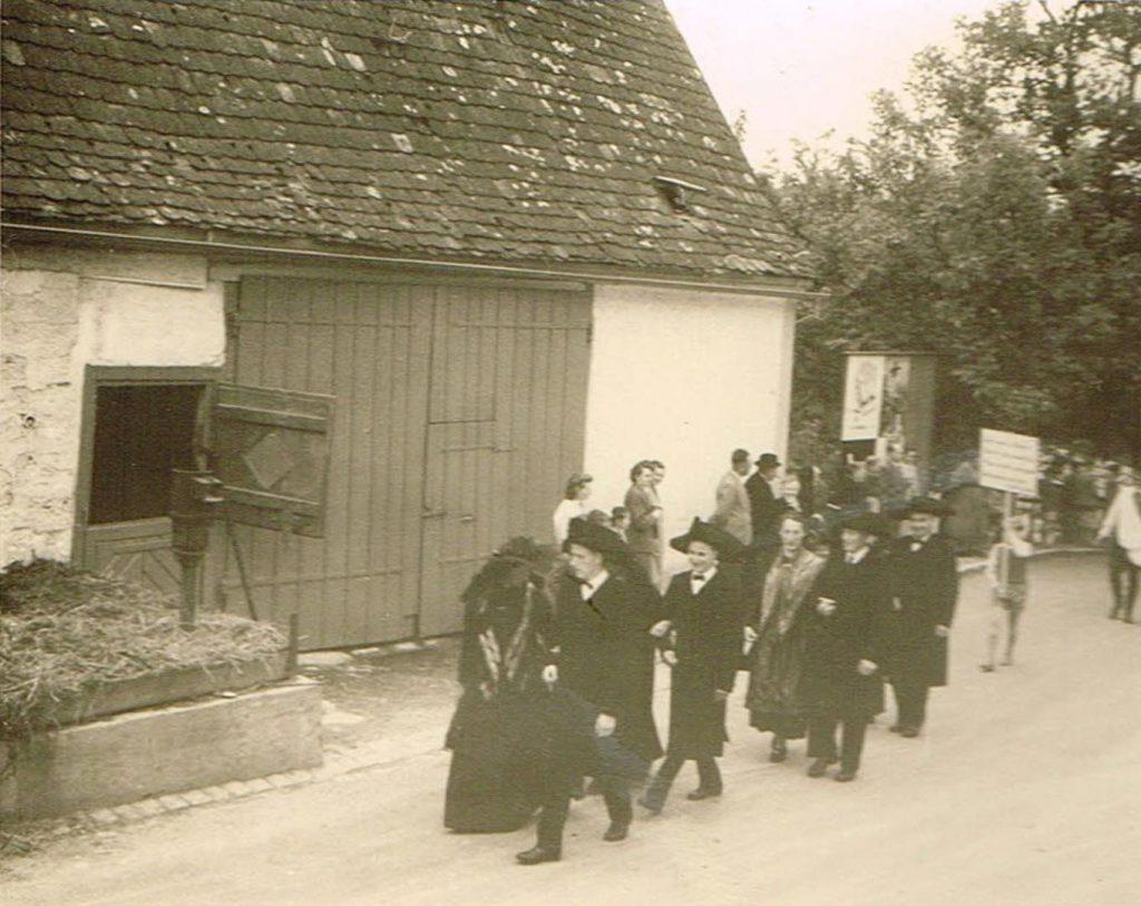 Trachtengruppe beim Heimattag 1957 vor dem Haus Bliesener. Das Haus mit Scheune und Miste zur Dorfstrasse stand zwischen dem Rathaus / Schulhaus und der heutigen Metzgerei Fritz.
