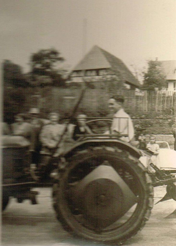 Roland Arnold auf Deutz mit Pflug beim Heimattag 1957. Die Menschen am linken Bildrand verdecken den Brunnen. Hinten in der Mitte ist die Pfarrscheune zu sehen, hinten rechts das Pfarrhaus.