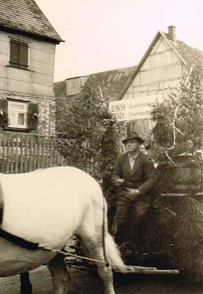 """Vermutlich der """"Bückeles-Bauer"""" Herrmann Düring beim Umzug des Heimattag 1957. Sein Wagen mit der Aufschrift """"EINST Gemütlichkeit – JETZT Finanzamt"""" wird von Pferden gezogen."""