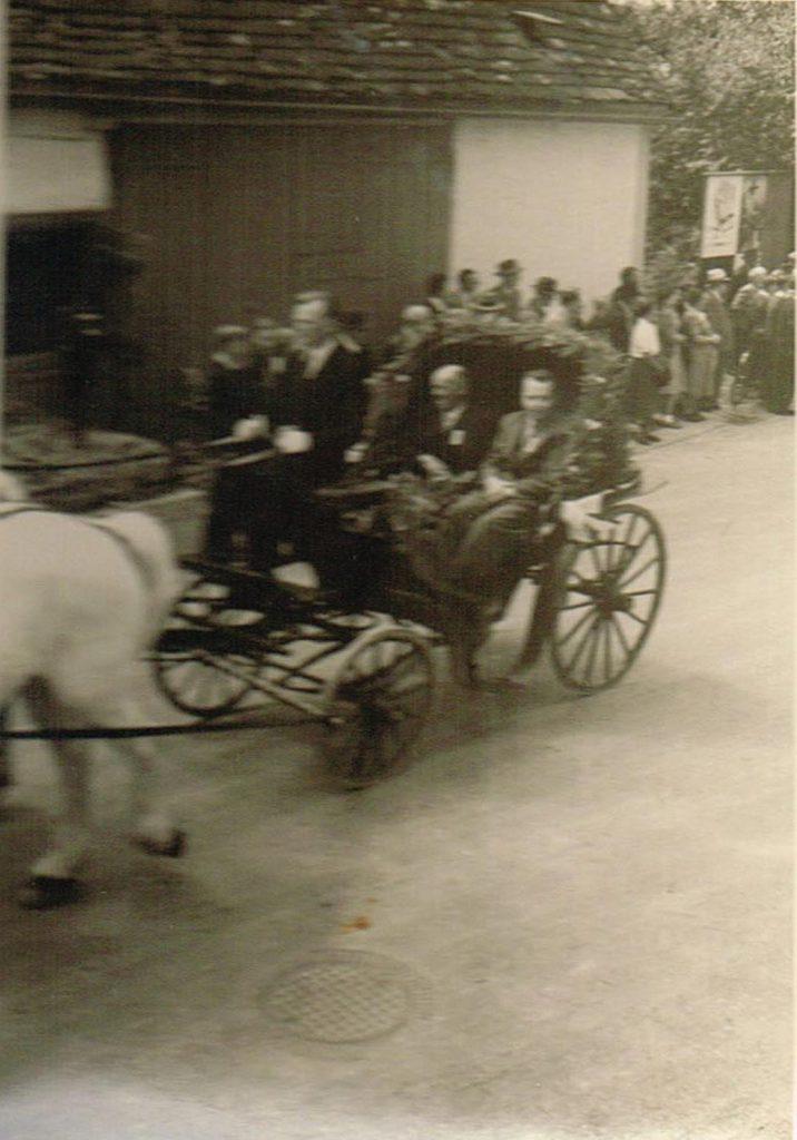Von Links: unbekannter Kutscher, mit Bürgermeister Gronbach, Pfarrer Günter in der Kutsche beim Heimattag 1957. Im Hintergrund die ehemalige Scheune von Bliesener.